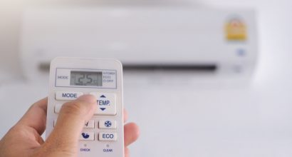 Hand holding remote control with air conditioner.